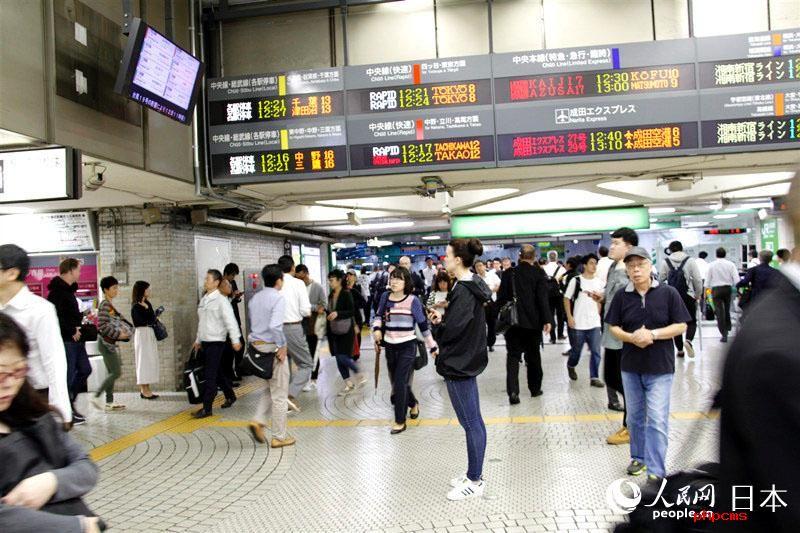 一名游客在东京新宿站通过电子屏幕查看最新铁路交通路运行情况。(李沐航 摄)